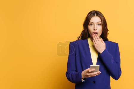 Photo for Shocked girl covering mouth with hand while holding smartphone on yellow background - Royalty Free Image