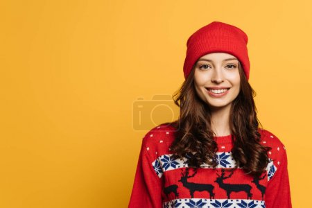 Photo for Happy girl in hat and red ornamental sweater smiling at camera isolated on yellow - Royalty Free Image