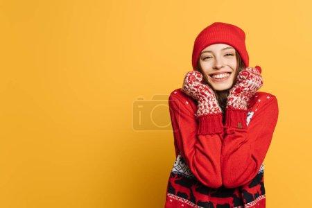 Photo pour Petite fille heureuse en chandail décoratif rouge et mitaines tenant les mains près du visage et souriant sur fond jaune - image libre de droit