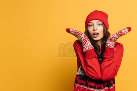Photo for Confused girl in red ornamental sweater and mittens showing shrug gesture on yellow background - Royalty Free Image
