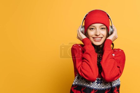 Photo for Smiling girl in hat and red ornamental sweater listening music in wireless headphones on yellow background - Royalty Free Image