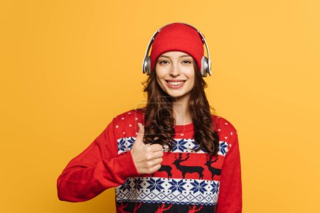 happy girl in wireless headphones on hat, in red ornamental sweater, showing thumb up isolated on yellow
