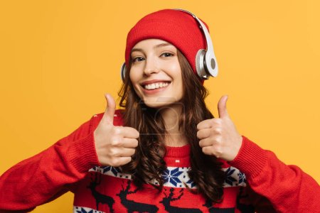 Photo for Happy girl in wireless headphones on hat, in red ornamental sweater, showing thumbs up on yellow background - Royalty Free Image