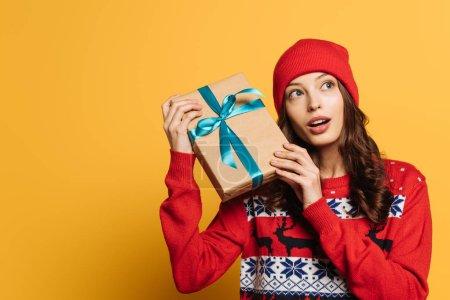 Photo pour Curieuse fille en chapeau et pull ornemental rouge tenant boîte cadeau sur fond jaune - image libre de droit