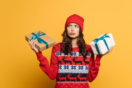 Photo for Thoughtful girl in hat and red ornamental sweater holding gift boxes on yellow background - Royalty Free Image