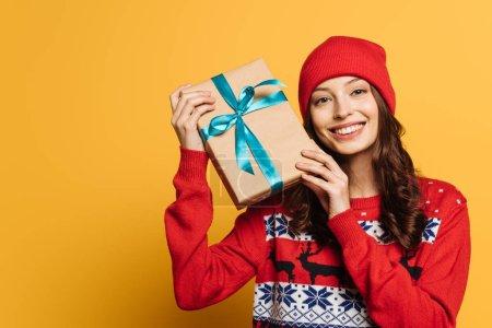 Photo pour Fille gaie en chapeau et pull ornemental rouge tenant boîte cadeau sur fond jaune - image libre de droit