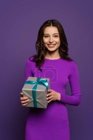 Photo pour Heureuse fille tenant boîte cadeau tout en souriant à la caméra sur fond violet - image libre de droit