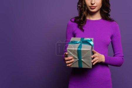Photo pour Vue recadrée de la jeune femme tenant boîte cadeau sur fond violet - image libre de droit