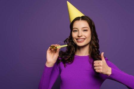 Photo pour Fille heureuse dans le chapeau de fête tenant corne de fête et montrant pouce vers le haut sur fond violet - image libre de droit