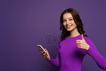 Photo for Cheerful girl holding smartphone and showing thumb up on purple background - Royalty Free Image