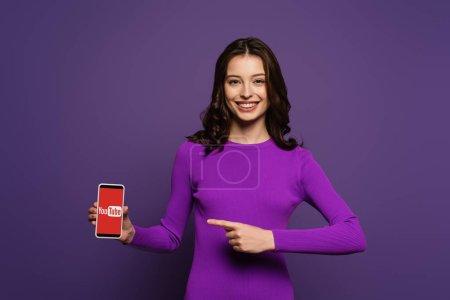 Photo pour KYIV, UKRAINE - 29 NOVEMBRE 2019 : fille souriante pointant du doigt le smartphone avec l'application Youtube à l'écran sur fond violet - image libre de droit