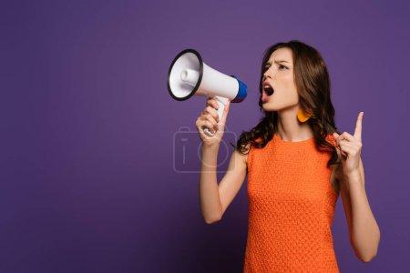 Photo pour Excitée fille crier en mégaphone et montrant geste d'attention sur fond violet - image libre de droit