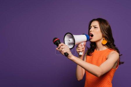 Photo pour Fillette excitée criant dans le mégaphone et le microphone en regardant loin sur fond violet - image libre de droit
