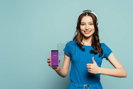 Photo for KYIV, UKRAINE - NOVEMBER 29, 2019: happy girl in wireless headphones showing thumb up while holding smartphone  with Instagram app on screen on blue background - Royalty Free Image