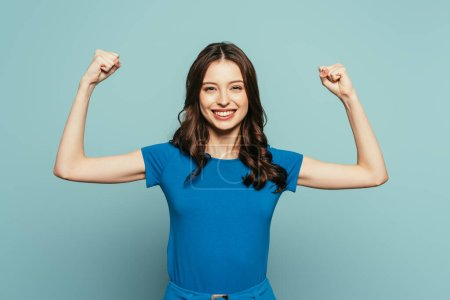 Photo for Cheerful girl showing winner gesture while smiling at camera on blue background - Royalty Free Image