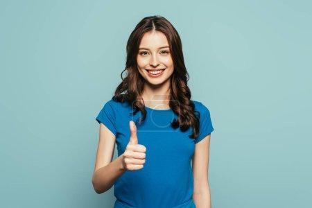 Foto de Chica feliz mostrando el pulgar hacia arriba mientras sonríe a la cámara aislada en azul - Imagen libre de derechos