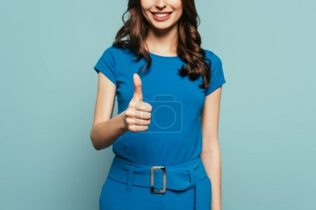 cropped view of smiling girl showing thumb up isolated on blue
