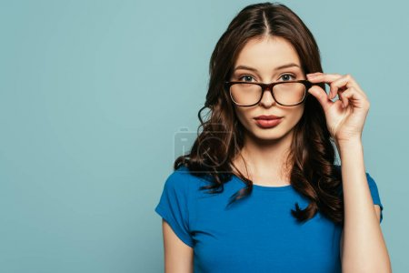 Photo for Attractive, confident girl touching glasses while looking at camera isolated on blue - Royalty Free Image