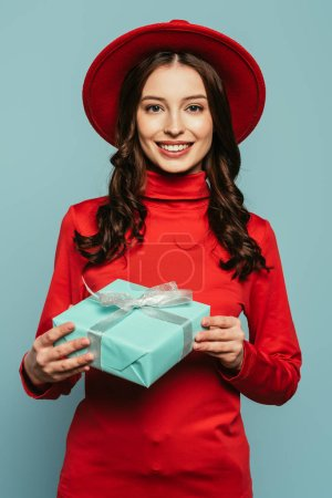 Photo for Cheerful stylish girl smiling at camera while holding gift box isolated on blue - Royalty Free Image