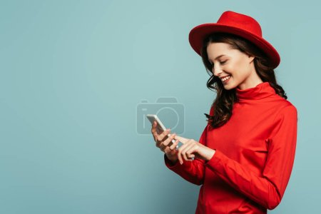 Photo for Happy stylish girl smiling while chatting on smartphone isolated on blue - Royalty Free Image