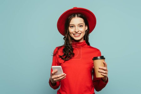alegre chica con estilo utilizando el teléfono inteligente mientras sostiene el café para ir aislado en azul