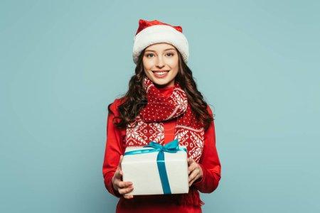 Photo pour Heureuse fille dans santa chapeau montrant boîte cadeau tout en regardant caméra isolée sur bleu - image libre de droit