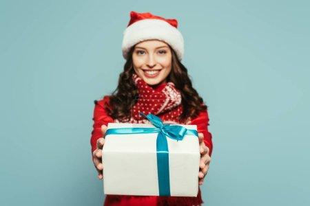 Photo pour Gaie fille dans santa chapeau montrant boîte cadeau tout en regardant la caméra sur fond bleu - image libre de droit