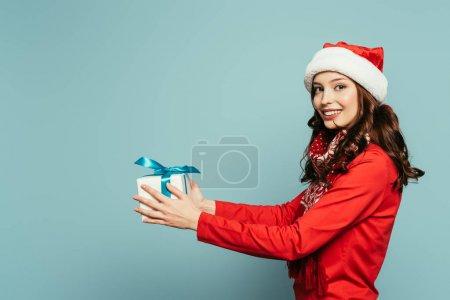 Photo pour Heureuse fille dans santa chapeau tenant boîte cadeau tout en regardant la caméra sur fond bleu - image libre de droit