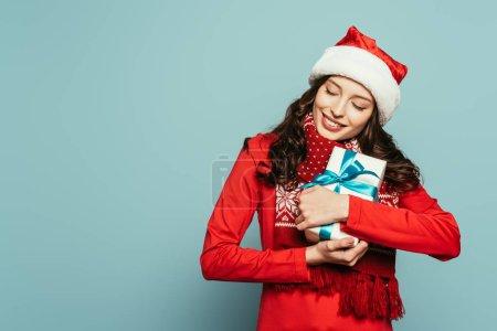 Photo pour Heureuse fille dans santa chapeau étreignant boîte cadeau avec les yeux fermés sur fond bleu - image libre de droit