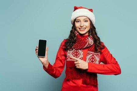 Photo pour Gaie fille en santa chapeau et pull rouge pointant avec le doigt au smartphone avec écran blanc sur fond bleu - image libre de droit