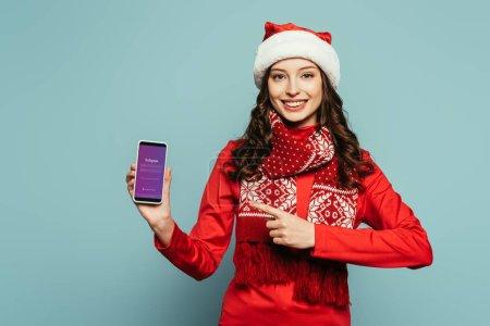 Photo pour 1KYIV, UKRAINE - 29 NOVEMBRE 2019 : fille heureuse en chapeau de Père Noël et pull rouge pointant du doigt le smartphone avec l'application Instagram à l'écran sur fond bleu - image libre de droit