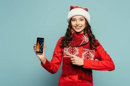 Photo pour Heureuse fille en santa chapeau et pull rouge pointant du doigt le smartphone avec des graphiques et des graphiques à l'écran sur fond bleu - image libre de droit