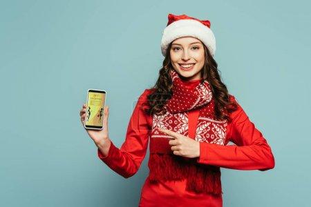Photo pour Heureuse fille en santa chapeau et pull rouge pointant du doigt le smartphone avec la meilleure application de shopping à l'écran sur fond bleu - image libre de droit