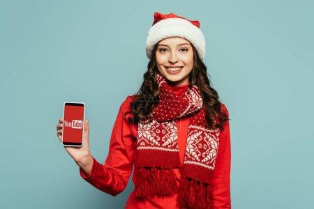 Photo pour KYIV, UKRAINE - 29 NOVEMBRE 2019 : fille heureuse en chapeau de Père Noël et pull rouge montrant smartphone avec application Youtube à l'écran sur fond bleu - image libre de droit