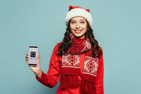 Photo pour 1KYIV, UKRAINE - 29 NOVEMBRE 2019 : fille heureuse en chapeau de Père Noël et pull rouge montrant smartphone avec application Uber à l'écran sur fond bleu - image libre de droit
