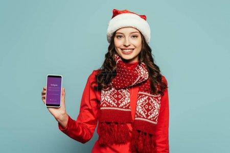 Photo pour KYIV, UKRAINE - 29 NOVEMBRE 2019 : gaie fille en chapeau de Père Noël et pull rouge montrant smartphone avec application Instagram à l'écran sur fond bleu - image libre de droit