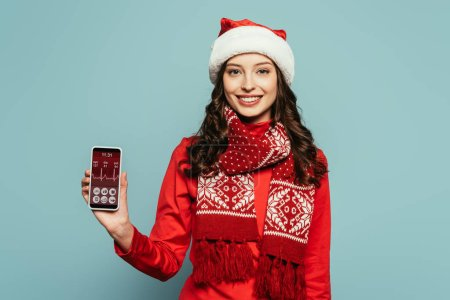 Photo for Cheerful girl in santa hat and red sweater showing smartphone with heartbeat rate on screen on blue background - Royalty Free Image
