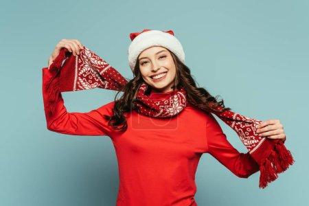 Photo pour Heureuse fille en santa chapeau touchant écharpe rouge et souriant à la caméra sur fond bleu - image libre de droit