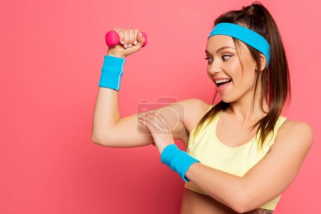 Photo for Excited sportswoman touching biceps while training with dumbbell on pink background - Royalty Free Image