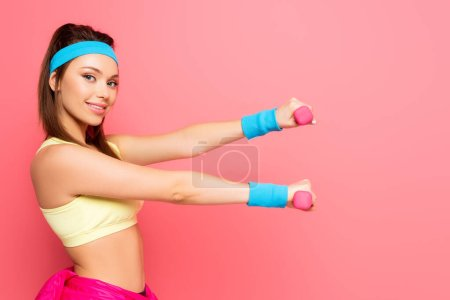 Photo for Attractive young sportswoman training with dumbbells while smiling at camera on pink background - Royalty Free Image