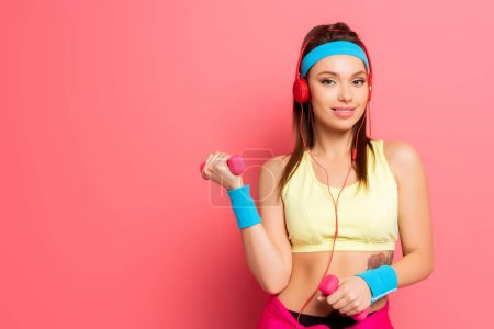 Photo for Smiling sportswoman in headphones training with dumbbells on pink background - Royalty Free Image