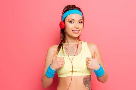 Foto de Feliz deportista joven en audífonos mostrando pulgares sobre fondo rosa - Imagen libre de derechos