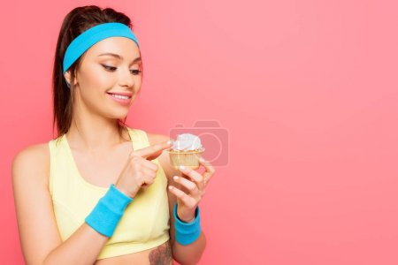 lächelnde Sportlerin berührt Schlagsahne auf leckerem Cupcake isoliert auf pink