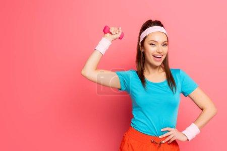 Photo pour Sportive heureuse faisant de l'exercice avec haltère tout en tenant la main sur la hanche sur fond rose - image libre de droit