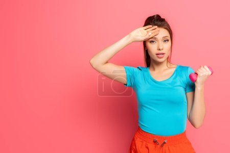tired sportswoman touching forehead while holding dumbbell on pink background