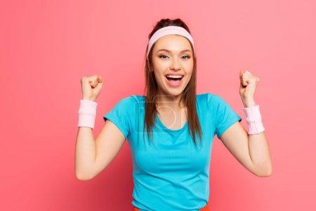 Photo pour Sportive gaie montrant geste gagnant tout en souriant à la caméra sur fond rose - image libre de droit