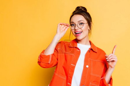 Photo for Happy student touching eyeglasses and showing idea gesture while looking at camera on yellow background - Royalty Free Image