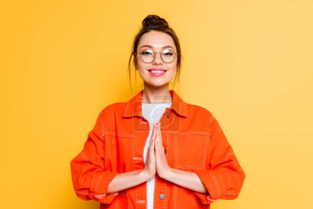 Photo for Smiling student in eyeglasses standing with praying hands isolated on yellow - Royalty Free Image