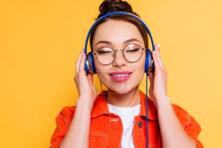 Photo pour Étudiant souriant dans des lunettes touchant écouteurs tout en étant debout avec les yeux fermés isolé sur jaune - image libre de droit