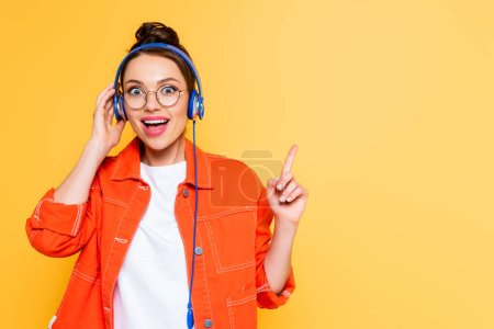 Photo for Excited student in headphones showing idea gesture isolated on yellow - Royalty Free Image